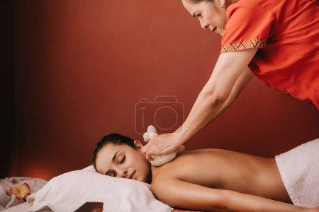 Photo pour Masseur asiatique faisant le massage de dos avec des boules de fines herbes à la femme dans le spa - image libre de droit