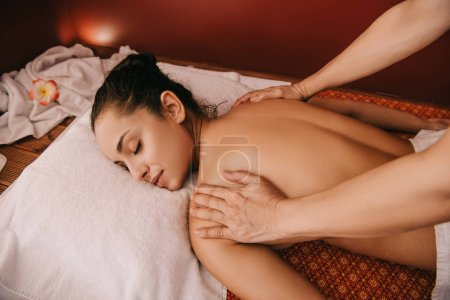 Photo for Cropped view of masseur doing back massage to woman on massage mat - Royalty Free Image