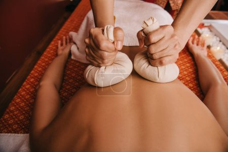 Photo for Cropped view of masseur doing back massage with herbal balls to woman in spa - Royalty Free Image