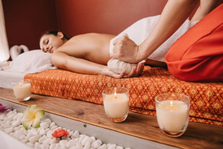 Photo for Cropped view of masseur doing massage with herbal ball to woman in spa - Royalty Free Image