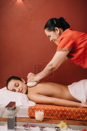 Photo for Side view of asian masseur doing back massage with herbal balls to woman in spa - Royalty Free Image