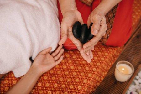 Photo pour Vue recadrée de masseur retenant des pierres chaudes pour le massage - image libre de droit