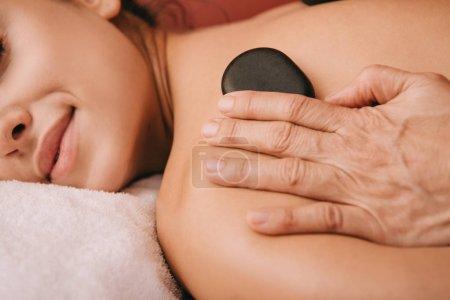 Photo pour Vue recadrée du masseur faisant massage aux pierres chaudes à la femme dans le salon de spa - image libre de droit