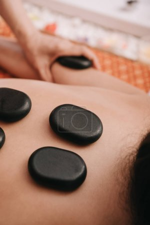 Photo for Cropped view of masseur doing hot stone massage to woman in spa salon - Royalty Free Image