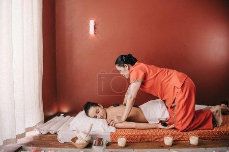 Photo pour Vue latérale du masseur asiatique faisant le massage chaud de pierre à la femme dans le salon de spa - image libre de droit
