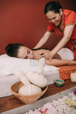 Photo for Selective focus of herbal balls and asian masseur doing hot stone massage - Royalty Free Image