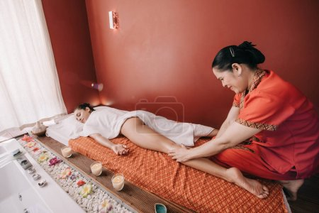 Photo for Asian masseur doing foot massage to woman in spa salon - Royalty Free Image
