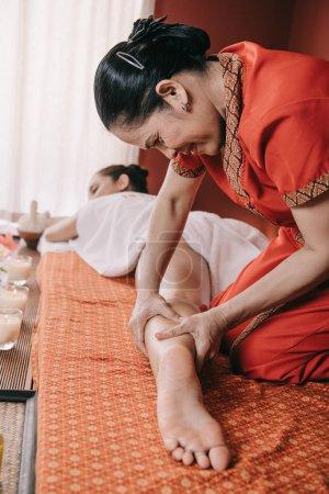 Photo pour Foyer sélectif du masseur asiatique faisant le massage de pied à la femme dans le salon de spa - image libre de droit