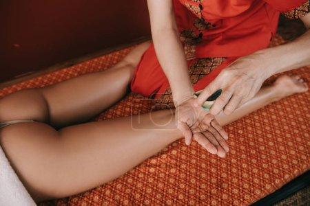 Photo pour Vue recadrée de masseur versant l'huile de parfum à la main dans le spa - image libre de droit