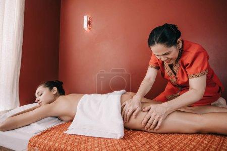 Photo pour Masseur asiatique faisant le massage de pied à la femme dans le salon de spa - image libre de droit