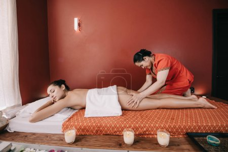 Photo for Side view of asian masseur doing foot massage to woman in spa salon - Royalty Free Image