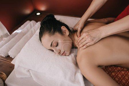 Photo pour Vue recadrée du masseur faisant massage du cou à la femme dans le salon de spa - image libre de droit