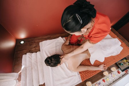 Photo for High angle view of masseur doing neck massage to woman in spa salon - Royalty Free Image
