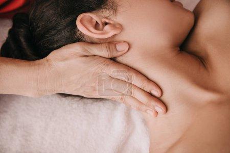 Photo pour Vue recadrée de masseur faisant le massage de cou à la femme dans le salon de spa - image libre de droit