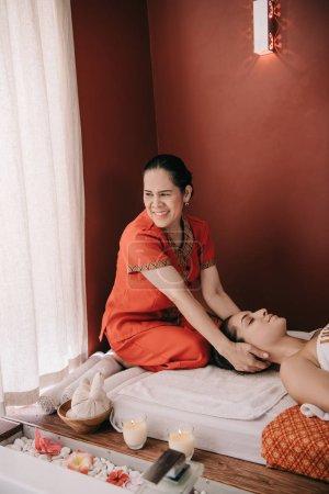 Photo pour Masseur asiatique souriant faisant le massage de cou à la femme dans le salon de spa - image libre de droit