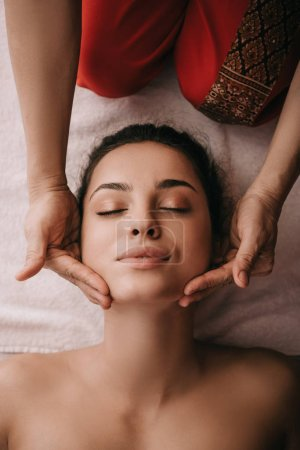 Photo pour Vue recadrée de masseur faisant le massage de visage à la femme dans le salon de spa - image libre de droit