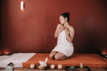 Photo pour Femme attirante avec les yeux fermés dans la serviette s'asseyant sur le tapis de massage - image libre de droit