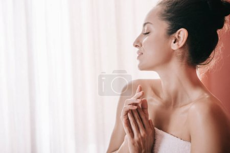 Photo pour Vue latérale de la femme attrayante avec les yeux fermés dans la serviette dans le salon de spa - image libre de droit