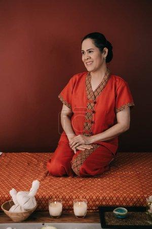 Photo pour Masseur asiatique dans le sourire rouge de costume et s'asseyant sur le tapis de massage - image libre de droit