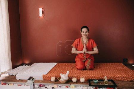Photo pour Masseur asiatique dans le sourire rouge de costume et affichant des mains de salutation - image libre de droit