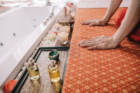 Photo pour Vue recadrée de masseur s'asseyant sur le tapis de massage dans le spa - image libre de droit