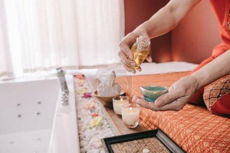 Photo pour Vue recadrée de masseur s'asseyant sur le tapis de massage et versant l'huile de parfum au bol - image libre de droit