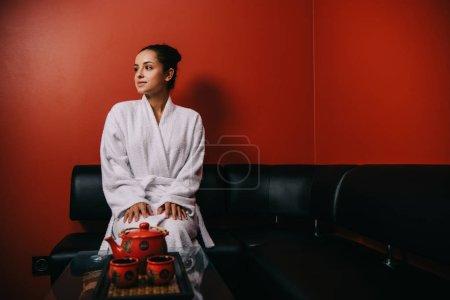 Photo pour Jolie femme en peignoir blanc assis sur le canapé et regardant loin - image libre de droit