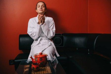 Photo pour Jolie femme en peignoir blanc avec les yeux fermés assis sur le canapé et tenant tasse - image libre de droit