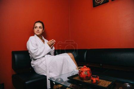 Photo pour Jolie femme en peignoir blanc assis sur le canapé et tenant tasse - image libre de droit