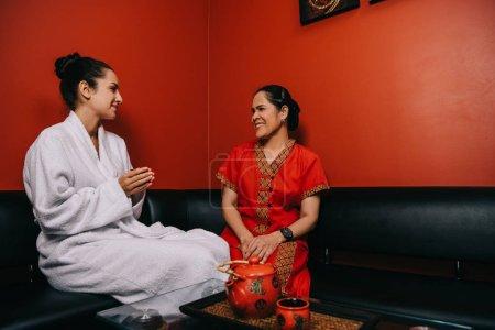 Photo pour Souriant femme en peignoir et asiatique masseur parler dans spa - image libre de droit
