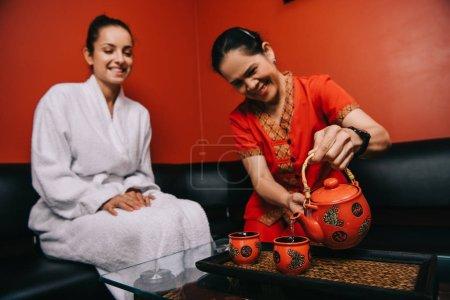 Photo pour Asiatique masseur verser thé à tasse et attrayant femme en peignoir souriant dans spa - image libre de droit