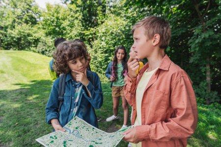 Photo pour Foyer sélectif de garçons réfléchis tenant carte proches amis - image libre de droit