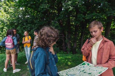 Foto de Selective focus of pensive boys holding map near friends - Imagen libre de derechos