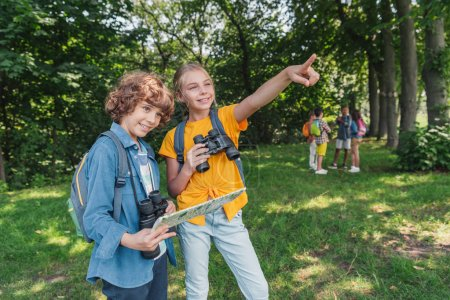 Foto de Selective focus of happy kid with binoculars pointing with finger near friend holding map - Imagen libre de derechos