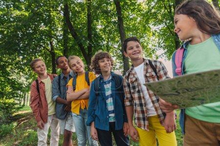 Photo pour Foyer sélectif des enfants multiculturels heureux près de la carte de tenue d'enfant - image libre de droit