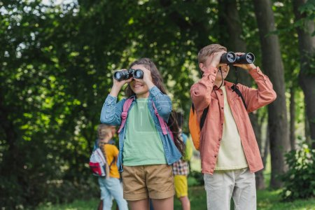 Photo for Selective focus of cheerful kids looking through binoculars in park - Royalty Free Image