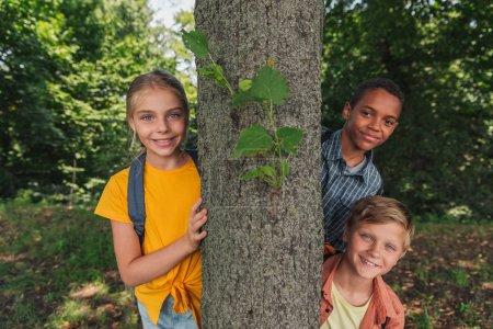 Photo pour Enfants multiculturels heureux souriant près du tronc d'arbre - image libre de droit