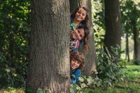 Photo pour Garçons heureux souriant près du tronc d'arbre avec l'ami adorable - image libre de droit