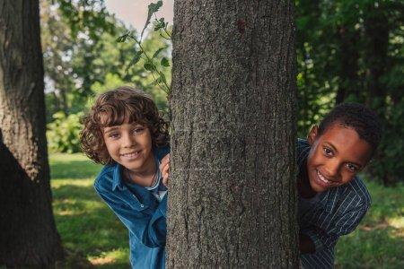 Photo pour Garçon bouclé mignon regardant l'appareil-photo près du tronc d'arbre et ami américain africain - image libre de droit
