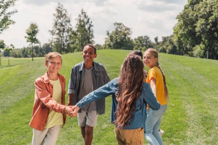 Foto de Happy multicultural kids holding hands and smiling in park - Imagen libre de derechos