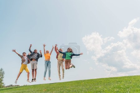 Foto de Happy multicultural kids jumping and gesturing against blue sky - Imagen libre de derechos