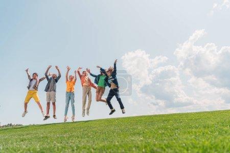 alegres niños multiculturales saltando y haciendo gestos contra el cielo azul