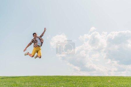 Photo pour Heureux garçon saut et geste contre ciel bleu - image libre de droit