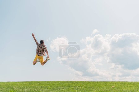 Photo for Back view of boy with outstretched hand jumping against blue sky - Royalty Free Image