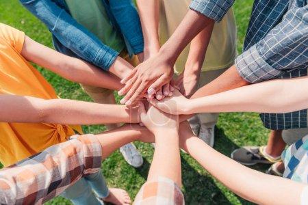 Photo pour Vue recadrée d'enfants multiculturels mettant les mains ensemble - image libre de droit