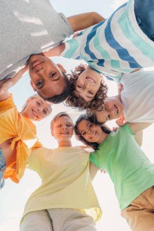 Foto de Vista inferior de los niños multiculturales positivos mirando la cámara - Imagen libre de derechos