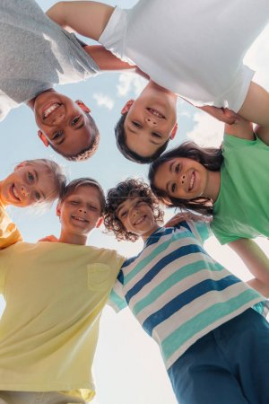 Photo for Bottom view of smiling multicultural children looking at camera - Royalty Free Image