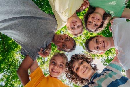 Photo pour Vue du bas des enfants multiculturels heureux regardant la caméra - image libre de droit