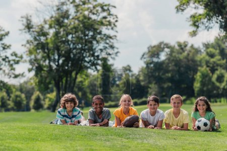 Foto de Happy multicultural kids lying on grass with balls - Imagen libre de derechos