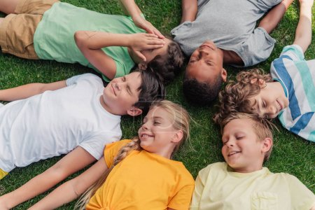 Foto de Overhead view of happy multicultural kids lying on grass - Imagen libre de derechos